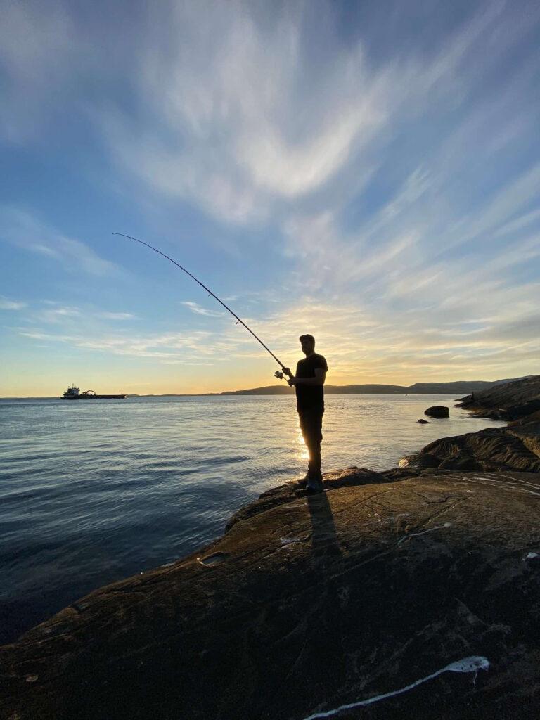 Mann som fisker fra land ved Saltstraumen